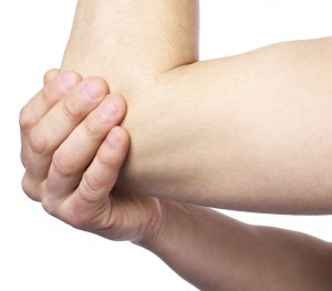 Hand holding an injured elbow
