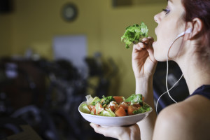 Young woman at the gym eating salad