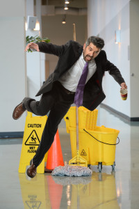 Businessman falling on wet floor inside office building